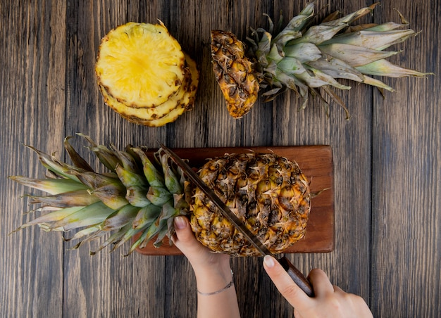 Top view of woman hands cutting pineapple with knife on cutting board with sliced pineapple on wooden table Free Photo