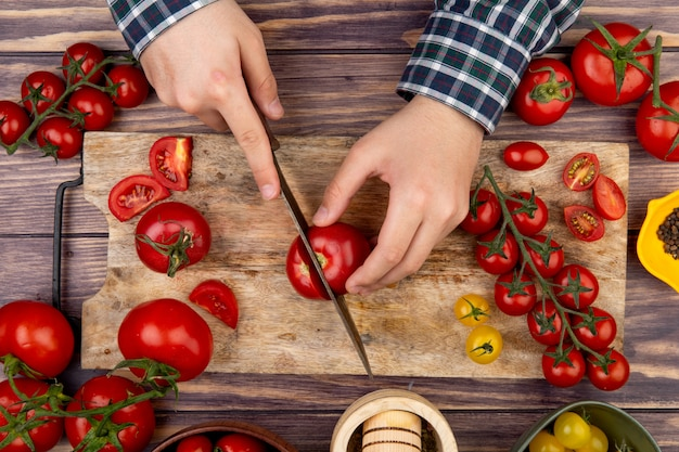 Top view of woman hands cutting tomato on cutting board with knife and black pepper garlic crusher on wooden surface