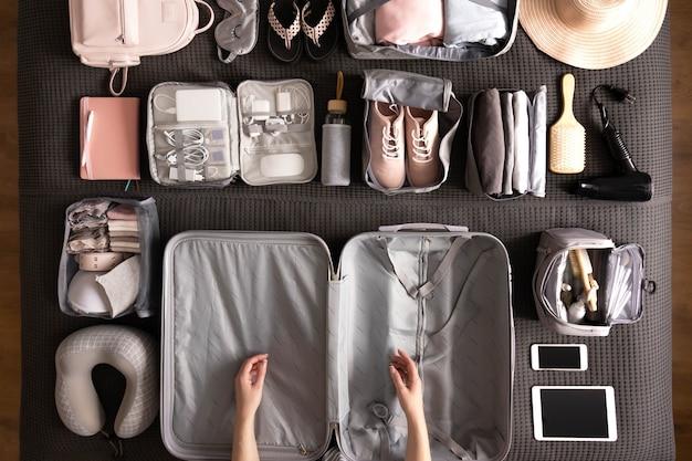 Вид сверху женские руки готовятся к поездке в отпуск, упаковывая чемодан, используя метод конмари