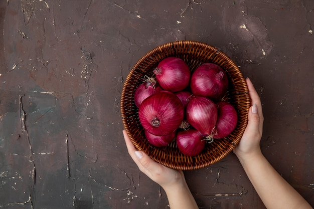 Top view of woman hands holding basket of onions on right side and maroon background with copy space