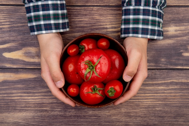 Top view of woman hands holding bowl of tomatoes on wooden table
