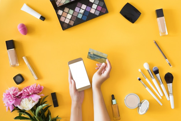 Top view of woman hands holding credit card, online shopping concept, beauty workspace with laptop, mobile phone, flowers and notebook, flat lay.