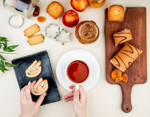 Top view of woman hands holding cup of tea and roll slice with jam, cookies, raisins and dried plums on white table