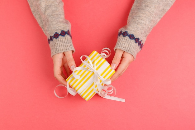 Top view of woman hands holding gift box on pink
