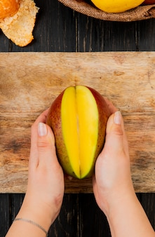 Top view of woman hands holding half cut mango on cutting board on wooden table