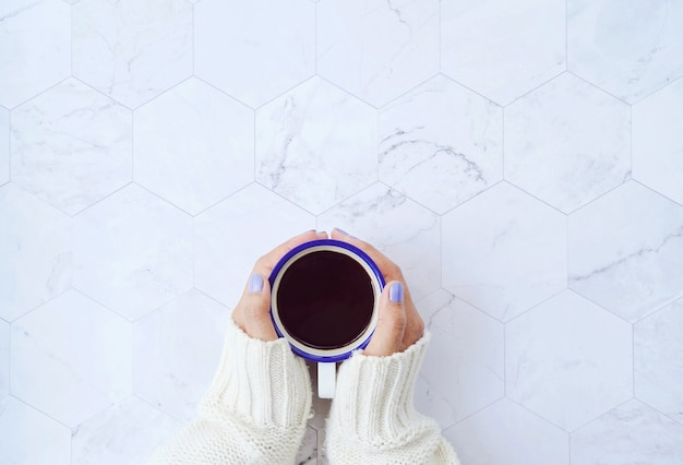 Top view of woman hands holding hot cup of coffee on white marble
