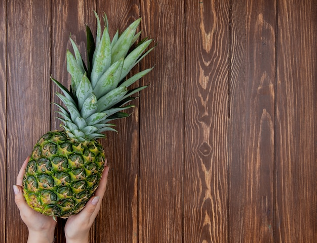 Top view of woman hands holding pineapple on left side and wooden background with copy space