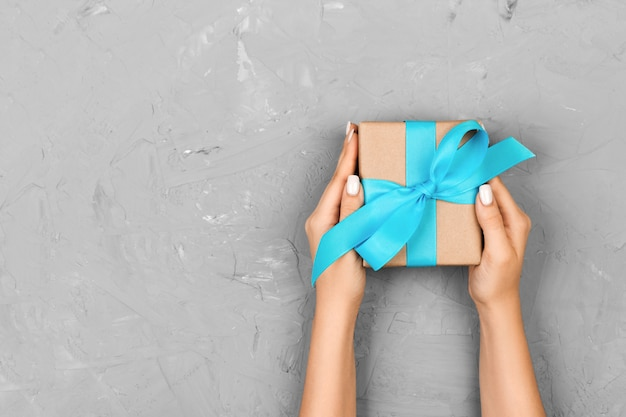 Top view woman hands holding present box with blue bow on gray with copy space