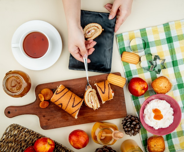 Top view of woman hands holding roll slice with fork on cutting board with dried plums, peaches, jams, cottage cheese ,cookies and pinecones and tea around on white table