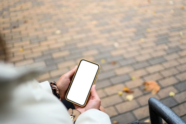 Top view of a woman hands holding smartphone with white blank screen. copy space in autumn garden. female reading text and watching video on a mobile phone.