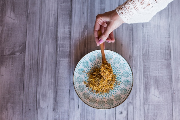 Top view of woman hands holding a spoon with yellow turmeric. grey wood table background. daytime, healthy lifestyle concept