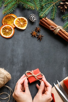 Top view of woman hands tie a bow on gift box with ribbon, sprig of conifer, cone, wrapping paper, scissors, cinnamon sticks, slices of orange on black surface. copy space. christmas theme.
