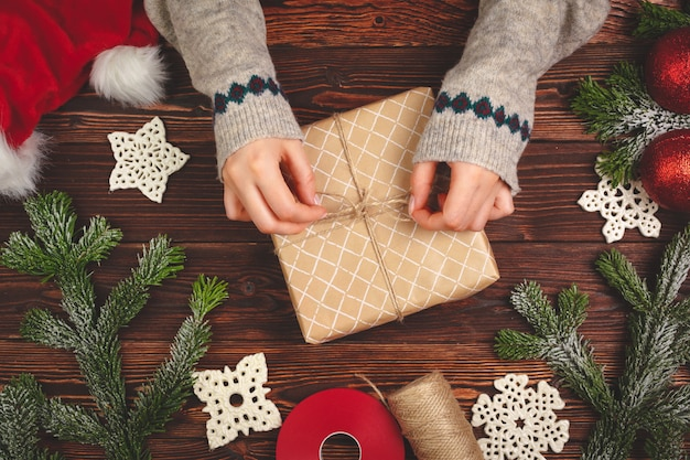 Top view of a woman hands with a christmas gift on wooden background