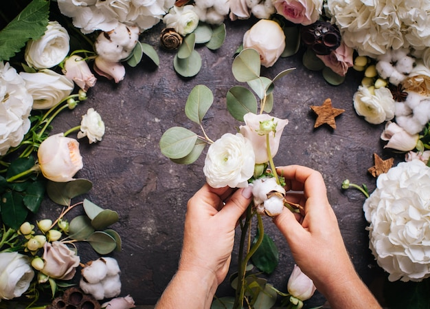 Top view of woman hands with flowers. florist is making stylish wedding composition, floristic design