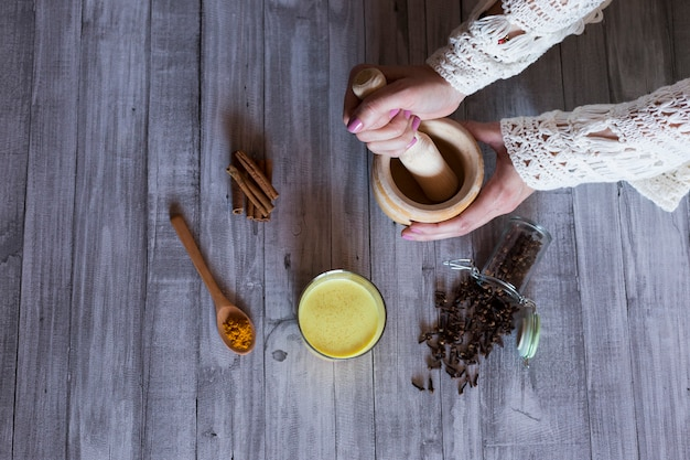 Top view of woman hands with ingredients on table, wooden mortar, yellow turmeric, clove and green natural leaves. close up, daytime