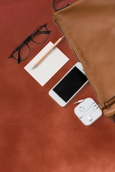 Top view of woman hipster traveler stuff with phone,notepad,glasses,and earphone