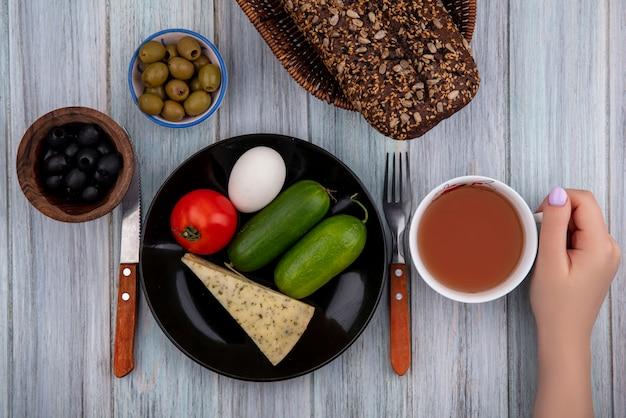 上面図の女性は、灰色の背景に黒と緑のオリーブとプレートにチーズきゅうりトマトと卵とお茶を保持します。