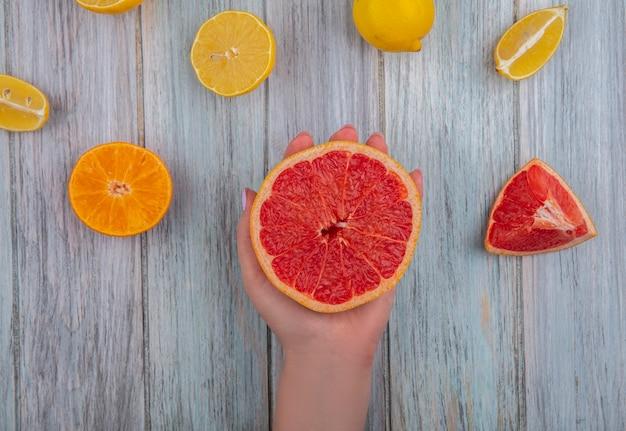상위 뷰 여자 회색 배경에 오렌지와 레몬 손에 절반 자몽 개최
