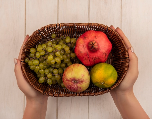 白い壁の上のバスケットにザクロのタンジェリンとブドウとリンゴを保持している上面図の女性