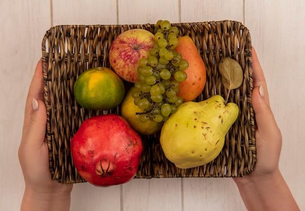 Donna di vista superiore che tiene la mela con il mandarino del melograno e la merce nel cestino dell'uva sulla parete bianca