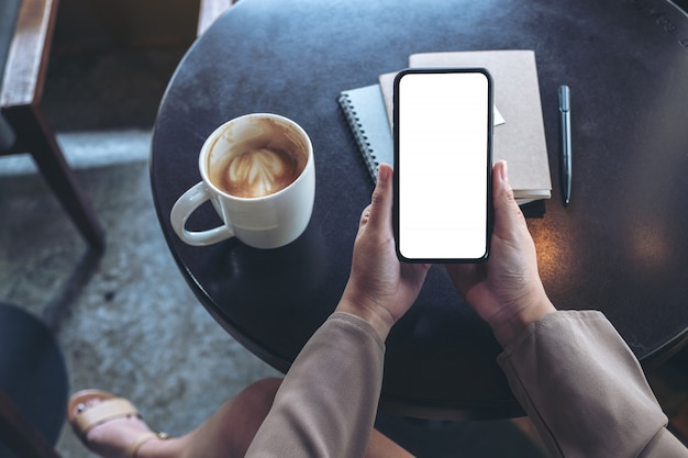Top view  woman holding black mobile phone with blank white screen with notebooks and coffee cup on table