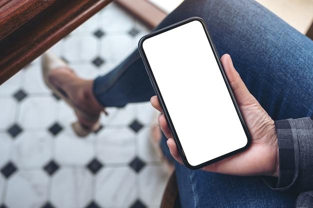 カフェに座っている間空白の白いデスクトップ画面で黒いスマートフォンを保持している上面図の女性