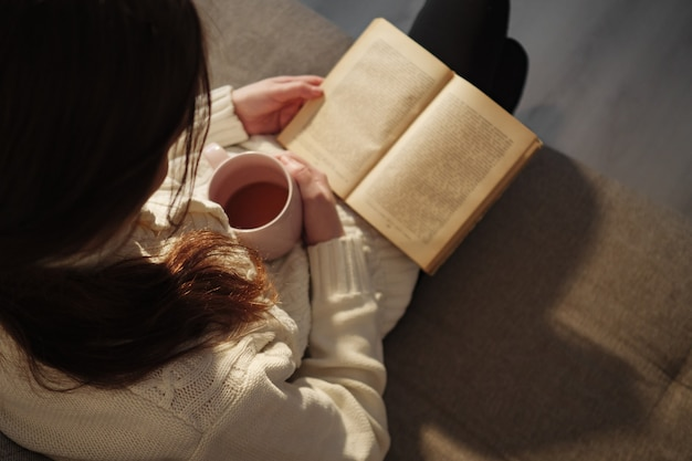 Top view of woman holding cup of tea and reading book.