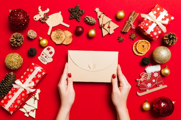 Top view of woman holding an envelope on red background made of holiday decations. christmas time concept