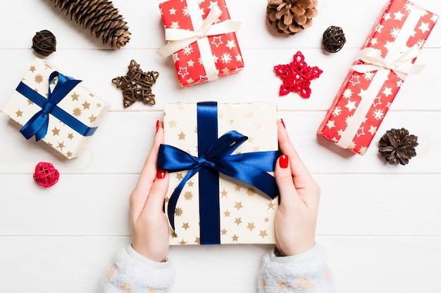 Top view of a woman holding a gift box in her hands on festive wooden surface