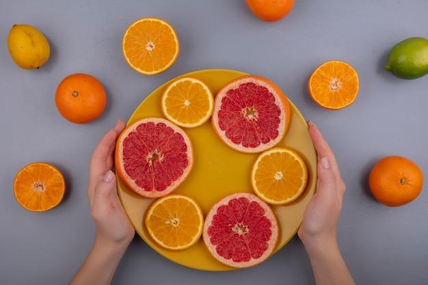 회색 배경에 노란색 접시에 오렌지와 자몽 슬라이스를 들고 상위 뷰 여자
