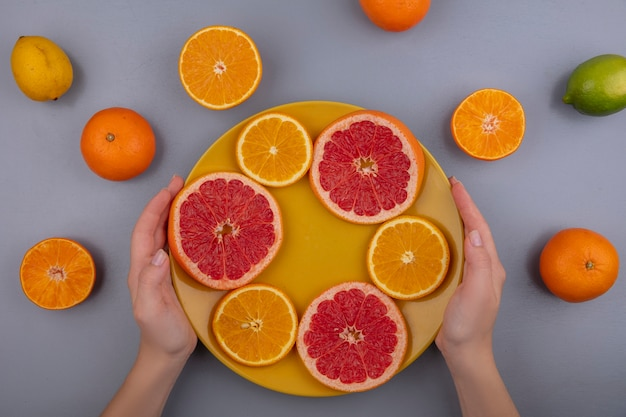 Donna di vista superiore che tiene le fette di pompelmo con le arance sulla zolla gialla su fondo grigio