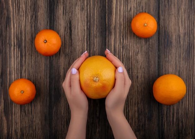 木製の背景にオレンジとグレープフルーツを保持している上面図の女性