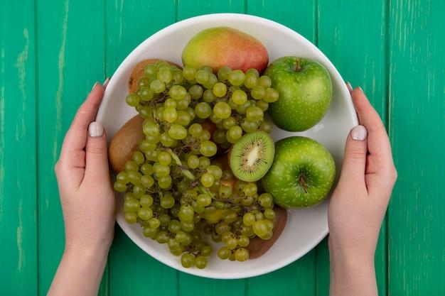 キウイ緑のブドウと緑の背景の上のプレートに梨と青リンゴを保持している上面図の女性
