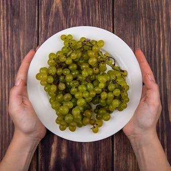 나무 벽에 접시에 녹색 포도 들고 상위 뷰 여자
