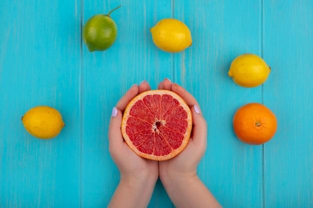 Donna di vista superiore che tiene mezzo pompelmo con lime e limoni su sfondo turchese