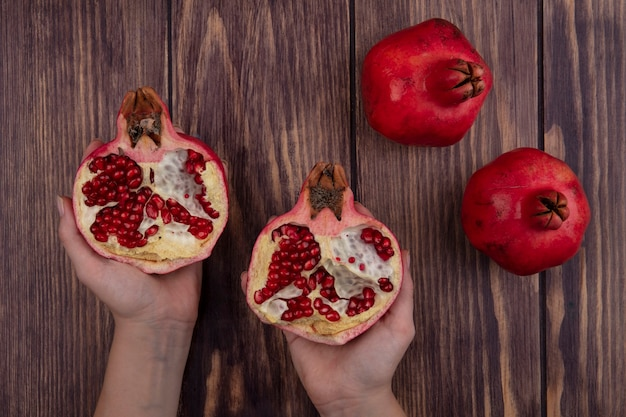 Top view woman holding halves of pomegranate in hands on wooden wall
