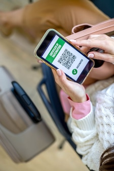 Вид сверху женщины, держащей удостоверение личности с сертификатом вакцины на экране смартфона в аэропорту