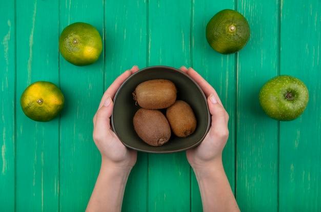 녹색 벽에 녹색 감귤 그릇에 키위를 들고 상위 뷰 여자