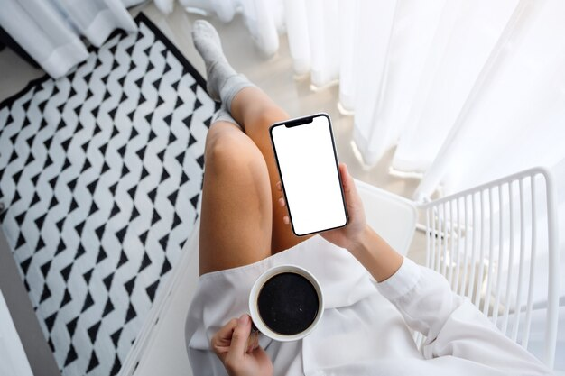 Top view  of woman holding mobile phone with blank white desktop screen while sitting and drinking coffee in bedroom