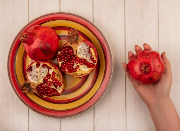 Donna vista dall'alto che tiene il melograno in mano e su un piatto su un muro bianco