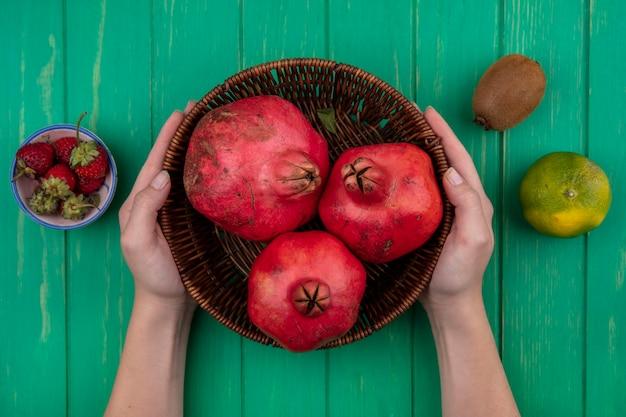 Donna di vista superiore che tiene i melograni in un cestino con il kiwi delle fragole ed i mandarini su una parete verde
