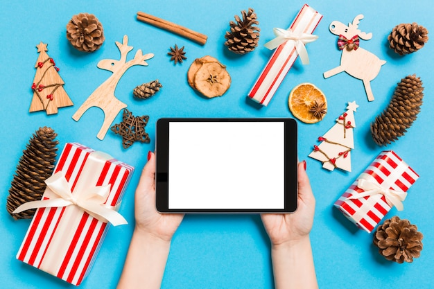 Top view of woman holding tablet in her hands on blue background made of christmas decations. new year holiday concept. mockup