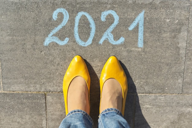 Top view on woman legs and 2021 text written in chalk on gray sidewalk