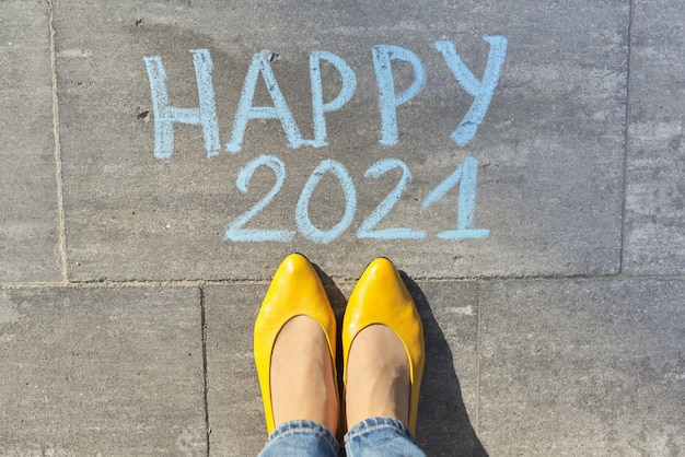 Top view on woman legs and happy 2021 text written in chalk on gray sidewalk