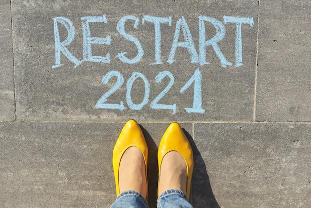 Top view on woman legs and restart 2021 text written in chalk on gray sidewalk