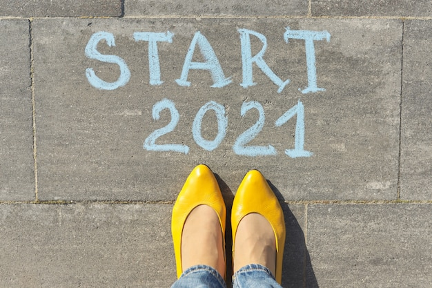 Top view on woman legs and start 2021 text written in chalk on gray sidewalk