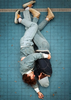 Top view woman and man lying on the floor while hugging