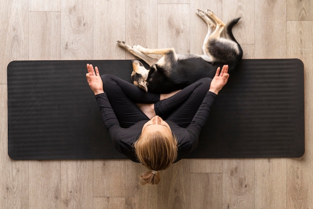 Top view woman meditating with dog