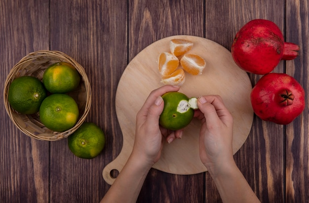 Vista dall'alto donna peeling buccia di mandarini verdi sul tagliere con melograni sulla parete di legno