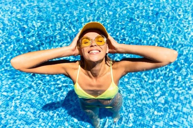 トップビューの女性がプールでポーズ